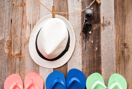 Bright flip flop sandals.  Hat and sunglasses  hanging on a line with wood background