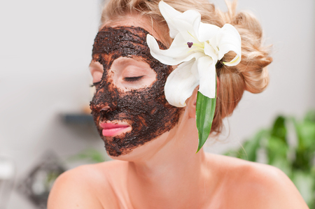 Beauty treatment and spa salon. Beautiful woman with facial mask at beauty salon