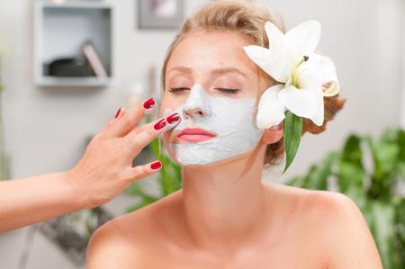 Beauty treatment and spa salon. Beautiful woman applying clay facial mask at beauty salon 版權商用圖片