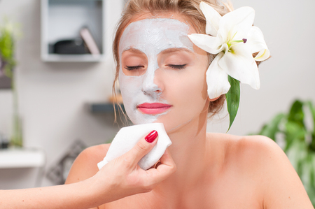 Beauty treatment and spa salon. Beautiful woman with clay facial mask at beauty salon 版權商用圖片