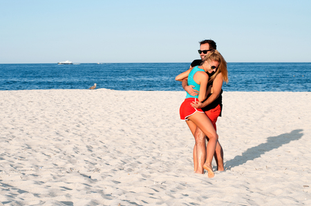 Happy young joyful couple having beach fun together during summer holidays vacation on tropical beach. Foto de archivo