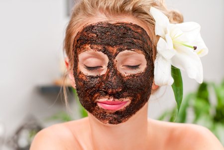 Beauty treatment and spa salon. Beautiful woman with facial mask at beauty salon