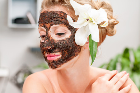 Beauty treatment and spa salon. Beautiful woman with chocolate facial mask at beauty salon