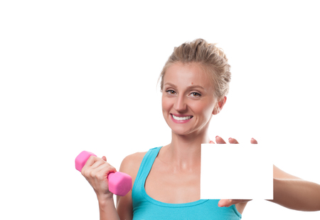 Woman with dumbbell showing empty paper card sign with copy space for text. Stock Photo