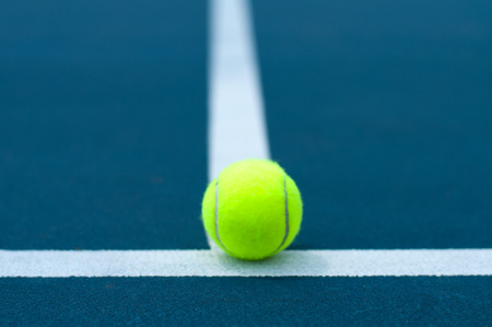 Close-up tennis ball on tennis court with white line