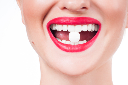 Perfect smile, red lips and white teeth. Female mouth with red lips and medicine pill