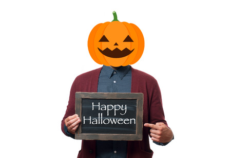Halloween concept, pumpkin head. Man with the head of a pumpkin holding chalkboard with text  Happy Halloween.