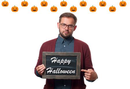 Halloween concept, pumpkin. Man holding chalkboard with text  Happy Halloween.