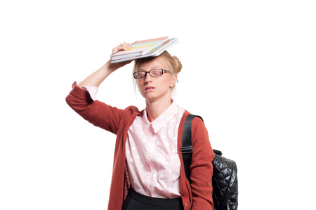 questions: Annoyed young student girl holding books, standing isolated on white background. Back to school