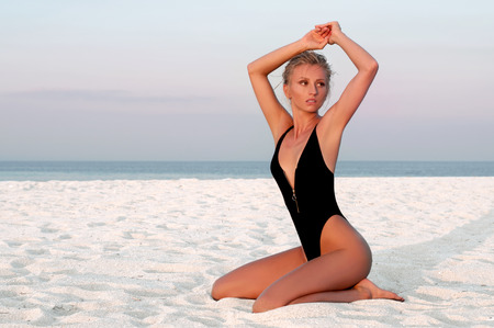 Beautiful woman in black swimsuit sitting on sand on the beach. Stock Photo