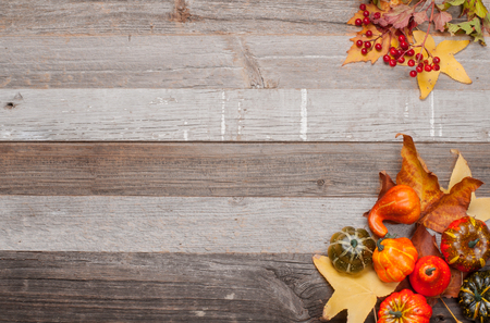 Pumpkins and fallen leaves on wooden background. Copy space for text. Halloween, Thanksgiving day or seasonal autumnal.