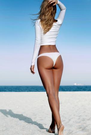 해변에 흰 수영복에서 아름 다운 소녀. 바다 해변에 그을린 된 여자의 패션 초상화