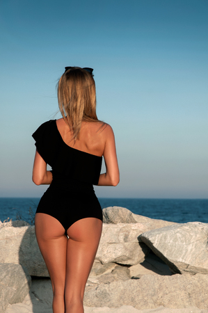Beautiful girl in a black swimsuit on the beach.  Sexy tanned buttocks on sea beach Imagens