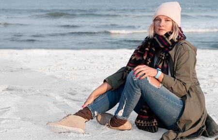 Beautiful woman sitting on lonely beach