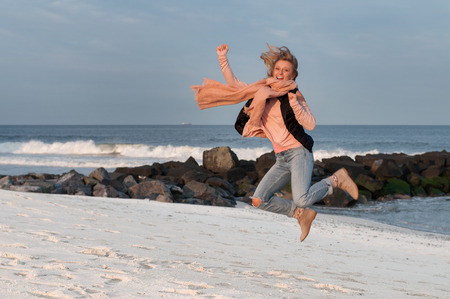 Happy woman jumping playfully on beach in autumn.