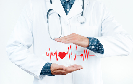 doctoring: Male Doctor with stethoscope is showing heart shape. Medical Insurance Concept