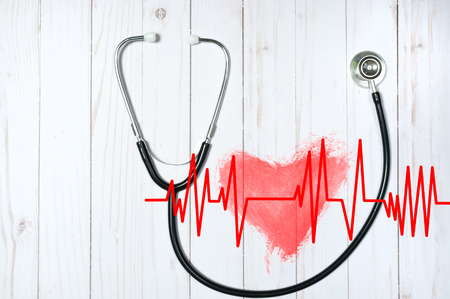 Medical stethoscope and red heart with cardiogram on desk. Health Concepts Stock Photo