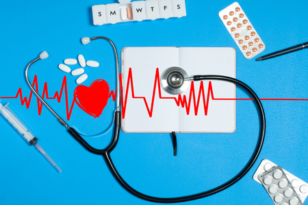 Workplace of doctor - stethoscope, notebook, medical items and pills on desk