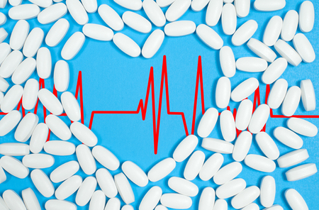 Heart shaped of white pills  on blue background