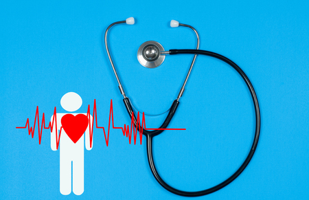 Medical stethoscope and red heart with cardiogram on blue background. Health Insurance Concepts