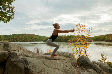 Portrait of beautiful young woman practicing yoga at outside. Girl doing squats exercises Stock Photo