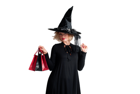 Halloween shopping. Happy woman in witch halloween costume with hat