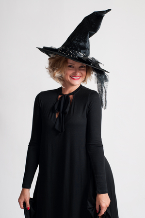 Happy woman in witch halloween costume with hat smiling on white background