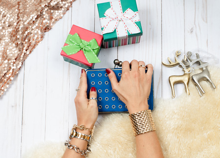 Female hands with jewelry and gift. Fashion accessories, wrist watches, glamor bracelets and rings Stock Photo