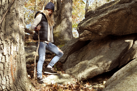 Girl walking in autumn forest in the mountains. Hiking, camp, adventure, traveling and friendship concept.