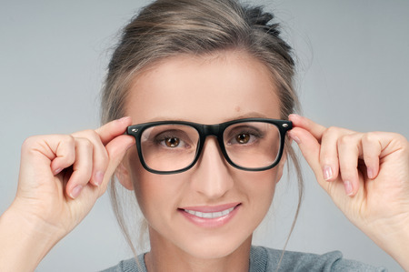 Beautiful young woman wearing glasses close-up. Checking new eyeglasses