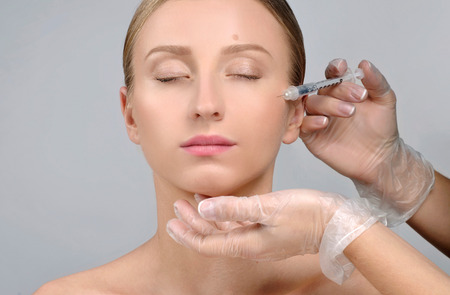Woman is getting botox injection. Anti-aging treatment and face lift. Cosmetic Treatment. Facial skin lifting injection to woman's face. Plastic Surgery