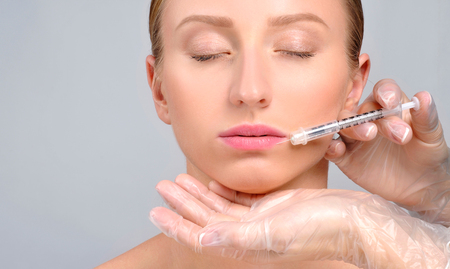 Woman is getting botox injection in lips. Cosmetic Treatment. Plastic Surgery. Beautiful girl receiving filler injection in lips