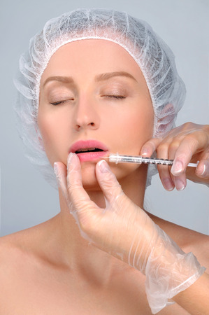 Beautiful girl receiving filler injection in lips. Cosmetic Treatment. Plastic Surgery. Banque d'images