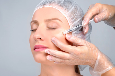 Woman is getting filler injection in cheeks. Anti-aging treatment and face lift. Cosmetic Treatment. Facial skin lifting injection to woman's face. Plastic Surgery 写真素材