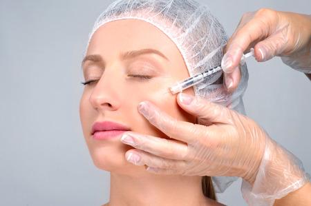 Mulher está recebendo injeção de enchimento nas bochechas. Tratamento antienvelhecimento e lifting facial. Tratamento cosmético. Pele facial, injeção de levantamento para o rosto da mulher. Cirurgia plástica Foto de archivo