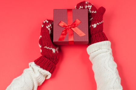 Female hands holding christmas gift box in red mittens Stock Photo