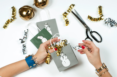 Christmas and New Year gift. Woman wearing bracelet. Christmas presents on a wooden table background Stock Photo