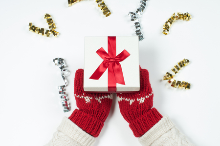 Female hands holding christmas gift box in red mittens 写真素材