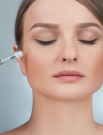 Woman is getting filler injection in cheeks. Anti-aging treatment and face lift. Cosmetic Treatment. Facial skin lifting injection to womans face. Plastic Surgery