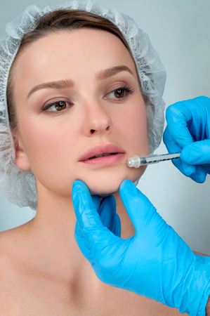 Beautiful girl receiving filler injection in lips. Cosmetic Treatment. Plastic Surgery. Standard-Bild