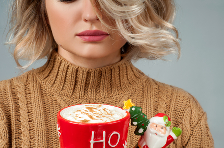Christmas and happy holiday concept. Close-up of a woman is holding a cup of coffee.
