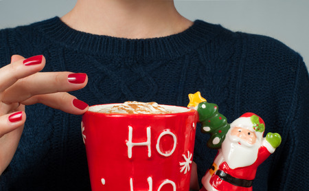 Christmas and happy holiday concept. Woman in warm sweater is holding a cup of coffee.