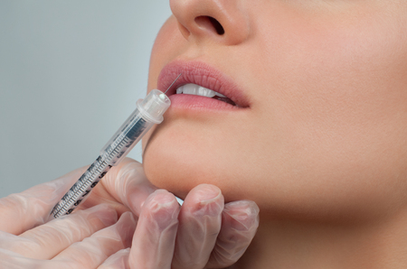 Beautiful girl receiving filler injection in lips. Cosmetic Treatment. Plastic Surgery. Stock Photo