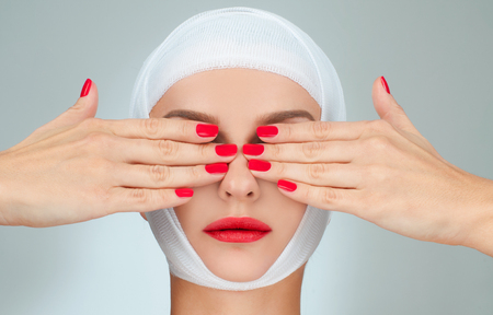 Woman covering eyes with bandaged head. Beauty, Fashion and Plastic Surgery concept