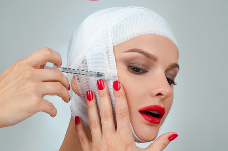 Woman get injection. Beautiful woman after plastic surgery with bandaged face. Beauty, Fashion and Plastic Surgery concept