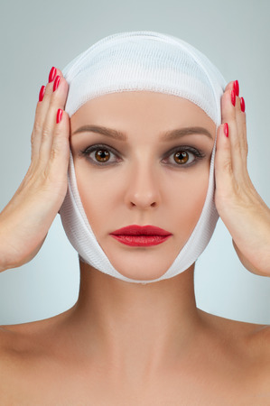 Patient in bandages. Beautiful woman after plastic surgery with bandaged face. Beauty, Fashion and Plastic Surgery concept