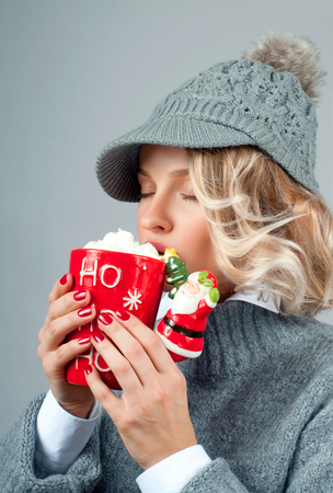 Christmas and happy holiday concept. Closeup of a woman in knitted hat is drinking coffee.