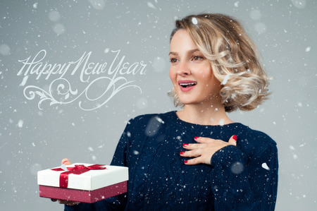 New Year. Woman in warm sweater is holding christmas gift Foto de archivo