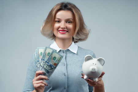 Woman holding piggy bank and bunch of money banknotes. Financial budget savings, smart investment concept