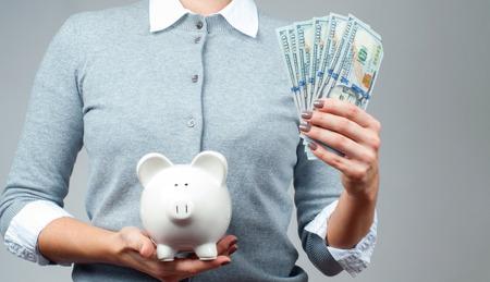 Frau, die Sparschwein und Bündel Geldbanknoten hält. Finanzielle Einsparungen, intelligente Anlagekonzept